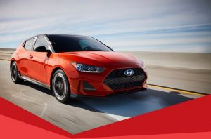 Hyundai Veloster flame red, driving on road, front right side view